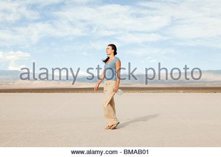 Woman in desert landscape with bottle - Stock Photo