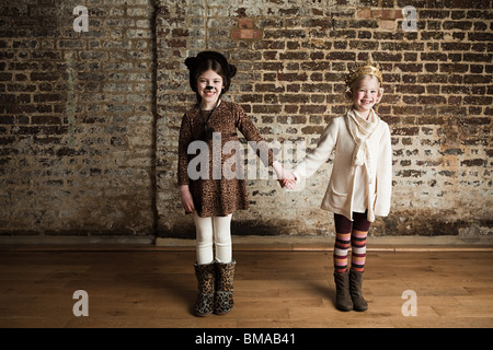 Young girls dressed up as cat and queen, holding hands - Stock Photo