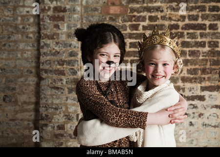 Young girls dressed up as cat and queen - Stock Photo