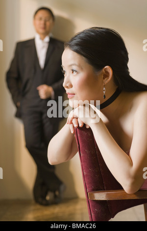 Woman Daydreaming with Man Standing in Background - Stock Photo