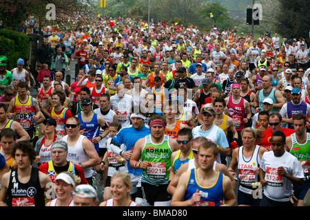 London Marathon runners running along Charlton Way, Blackheath, London, UK - Stock Photo