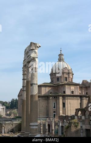 Rome, Italy. Three columns of the Foro di Cesare and church Santi Luca e Martina by Pietro da Cortona in the background. - Stock Photo