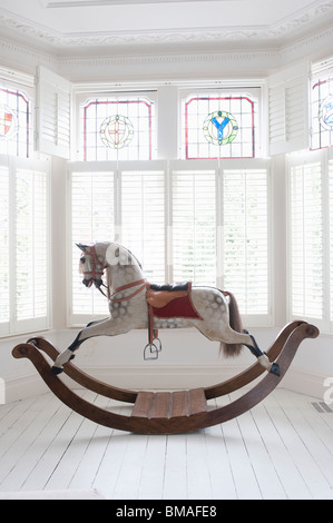 Antique rocking horse in bay window with stained glass, London - Stock Photo