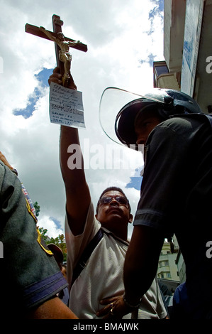 A supporter of Venezuela's President Hugo Chavez holds up a crucifix behind a police line during a protest in Caracas,Venezuela.