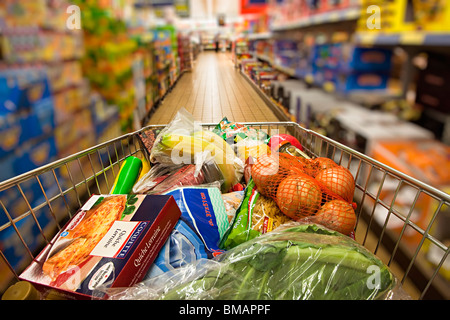 Shopping trolley being pushed down Lidl supermarket aisle Wales UK with person blurred in background - Stock Photo