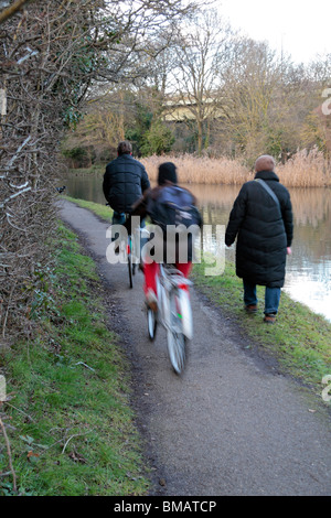 Cyclists passing a pedestrian on a path beside the Grand Union Canal in Brentford, Middx. (bikes blurry) - Stock Photo