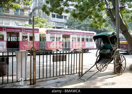 Empty hand rickshaw and tram on road ; Calcutta now Kolkata ; West Bengal ; India - Stock Photo