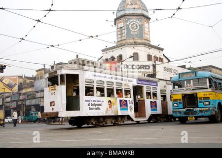 Street scene ; tram and bus on road ; Calcutta now Kolkata ; West Bengal ; India - Stock Photo