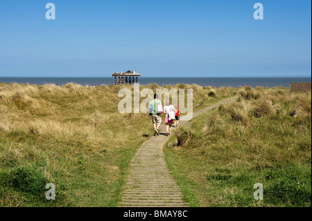 A family walking along a path leading down to Sizewell beach in Suffolk.  Photo by Gordon Scammell - Stock Photo