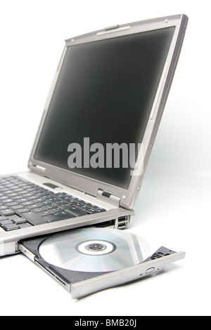 cd or dvd disk in the drive of a laptop - Stock Photo