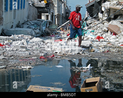 A man in reflected in a puddle as he walks through rubble and rubbish in Port au Prince after the Haiti earthquake - Stock Photo