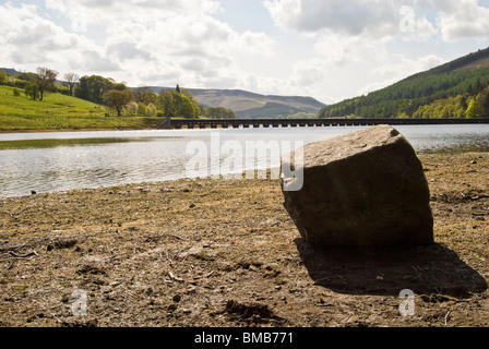 view ladybower derwent reservoir peak district derbyshire exposed rock boulder during dry spell pipe line viaduct - Stock Photo
