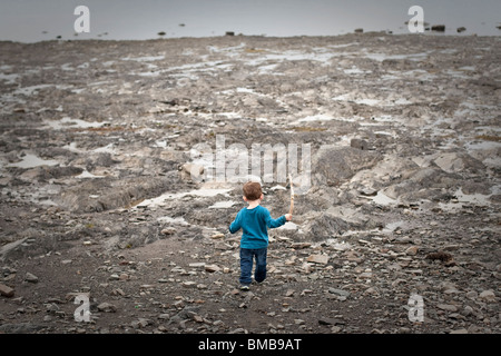 A two years old kid walks on a shingle beach with a stick in his hand - Stock Photo