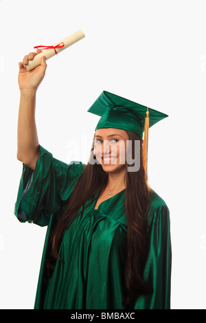 female college graduate in cap and gown with diploma - Stock Photo