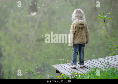 Stock photo of a four year old girl standing on her own by the side of a pond. - Stock Photo