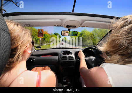 Open top car with female driver and passenger on open road