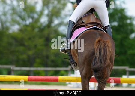 Stock photo of a horse and rider taking a jump at a show jumping competition. - Stock Photo