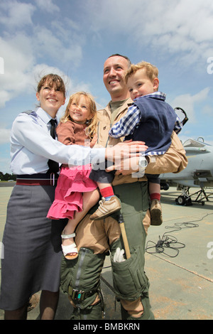 Sqn Ldr Nathan Giles, Holly Giles, Edward Giles & wife Sqn Ldr Anne Giles pose together after being reunited at - Stock Photo