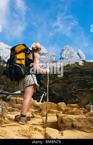 Hiker on Mt Kinabalu trail with the mountain peak in the background. Kinabalu National Park, Sabah, Borneo, Malaysia. - Stock Photo