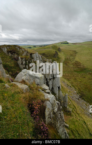 A wall of rock near Walltown Crags, Northumberland. Hadrian's Wall runs along the top of the hills in the distance. - Stock Photo