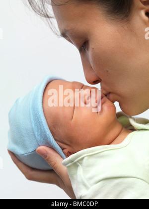 Mother kissing a sleeping newborn child baby boy on his cheek - Stock Photo