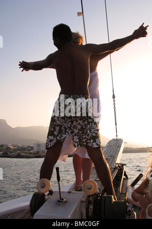 KYRENIA, NORTH CYPRUS. A young couple standing on the prow of a Turkish gulet and sailing into the setting sun. - Stock Photo