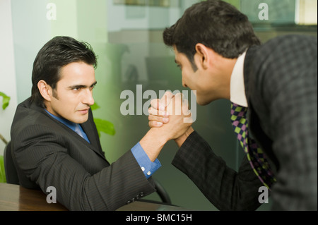 Two businessmen arm wrestling in an office - Stock Photo