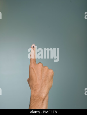 Close-up of a man's hand showing voting ink mark on his index finger - Stock Photo