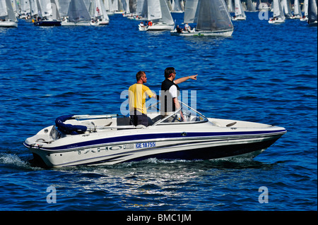 Two spectators in a powerboat watching the start of the Bol d'Or yacht race on lac Leman (Lake Geneva) 2009 and - Stock Photo