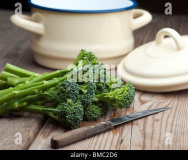 Fresh Broccoli Laid On A Wooden Kitchen Table With A Vegetable Knife and A Pan With Lid In The Background - Stock Photo