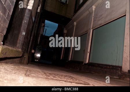 Warrington town backstreets dark alley at night. Mysterious and moody dangerous alley. Pavement at the back of shops - Stock Photo
