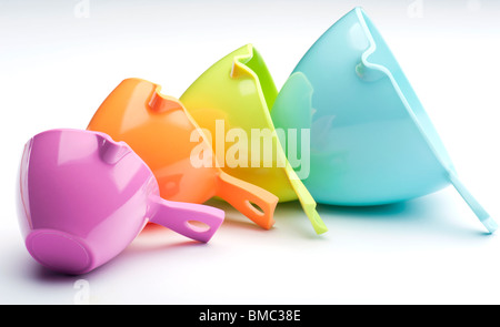 Four Plastic Measuring Cups Laid On A White Background - Stock Photo