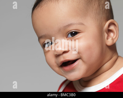 Portrait of a cute smiling little child. Nine months old baby girl. - Stock Photo