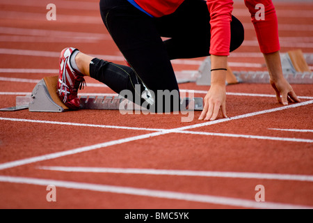 On the starting line. Young woman prepares to sprint to success - Stock Photo