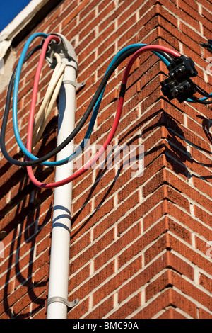 Some loose hydro wires made up of a red, blue and a black line, coming out of a conduit attached the side of a brick wall.