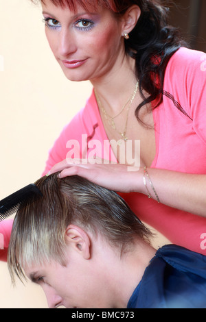 Portrait of professional hairdresser cutting man's hair - Stock Photo