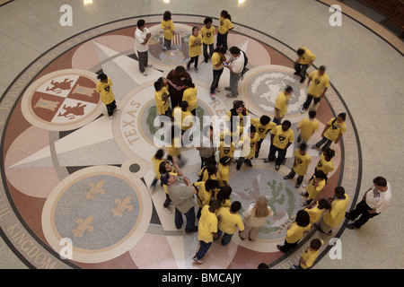 School children looking at seals on floor of Texas state capitol building rotunda in Austin - Stock Photo