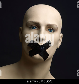 Dummy, mannequin, tape over mouth - censorship / secrecy / gagging / silence / free speech concept - Stock Photo