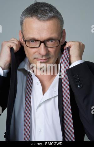 Portrait of Businessman getting Dressed - Stock Photo