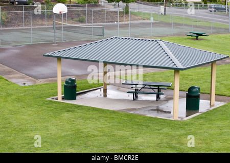 Covered picnic area in new neighborhood park.  Tennis court and 1/2 basketball court in the background. - Stock Photo