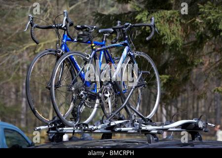 racing touring bikes on a roofrack on a car in a forest carpark derbyshire england uk - Stock Photo