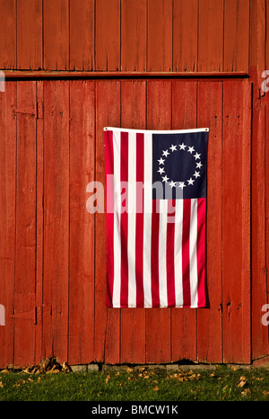 Close up replica of a vintage American flag, 13 stars and srripes, Betsy Ross on old red barn, New Jersey, United - Stock Photo