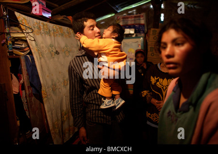 One-year-old Alondra Viveros lies in her father's arms in her mother's modest home, San Antonio Albarranes, Mexico. - Stock Photo