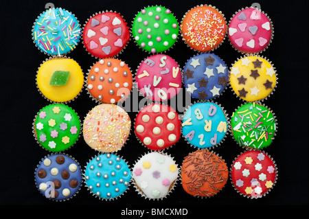 Colourful mini cupcakes on a black background - Stock Photo
