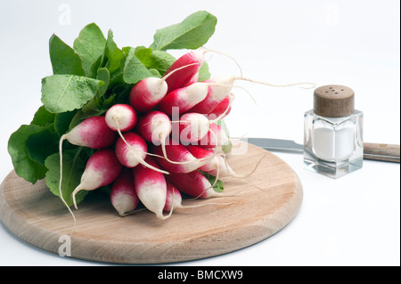 French Breakfast Radish On A Wooden Chopping Board, With A Salt Pot and Knife, Against A White Background - Stock Photo