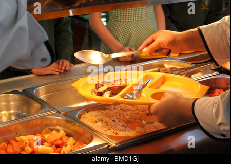 Dinner lady serves up school meals on a yellow plastic tray to primary school pupils waiting at the hot plate in - Stock Photo