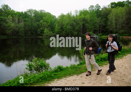 Two teenage hikers walking along Sunrise Lake on the Patriot's Path trail in Jockey Hollow near Morristown, New - Stock Photo