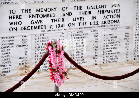 Memorial inscription with offering of lei draped over ropes, USS Arizona Memorial, Pearl Harbor, Oahu, Hawaii, USA - Stock Photo