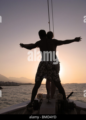 A young couple sailing into the setting sun on a Turkish gulet. North Cyprus, 2009. - Stock Photo