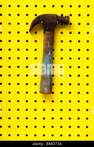 Old hammer with paint marks hangs from metal hook. Wooden handle with metal head. - Stock Photo